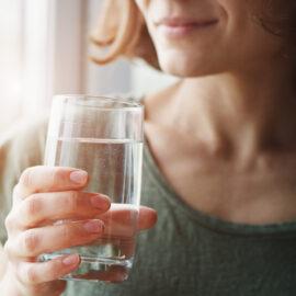imagem de uma mulher segurando um copo de água