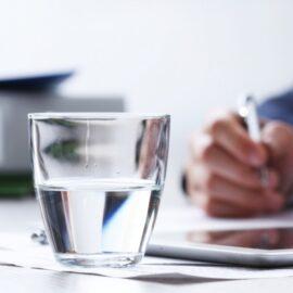 imagem de uma pessoa trabalhando e um copo de água em cima da mesa